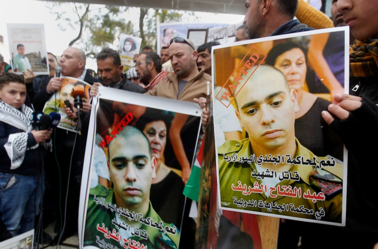A Palestinian holds a poster of Israeli Sergeant Elor Azaria that reads
