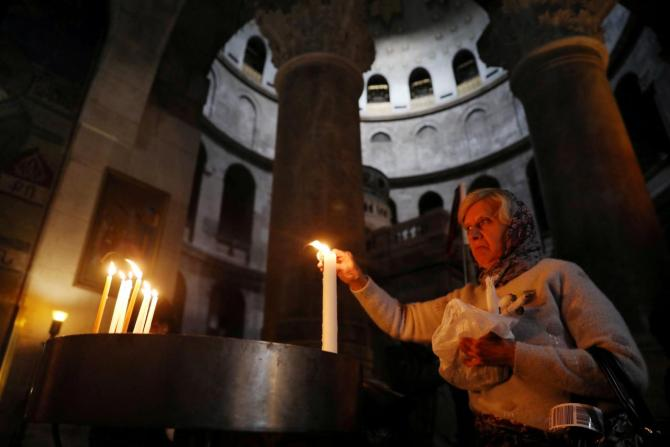FILE PHOTO: A worshipper lights a candle as she visits the Church of the Holy Sepulchre in Jerusalem's Old City