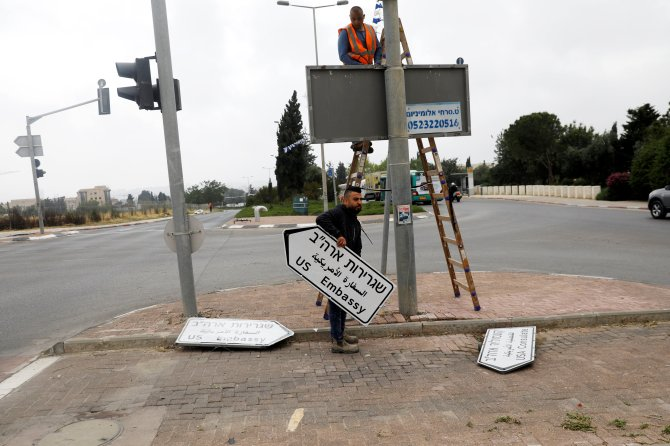 FILE PHOTO: A worker holds a road sign directing to the U.S. embassy, in the area of the U.S. consulate in Jerusalem