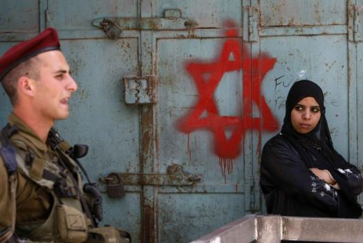 An Israeli soldier keeps guard near a Palestinian woman standing by a Star of David graffiti sprayed by Israeli settlers near an army checkpoint in the centre of the occupied West Bank city of Hebron on May 18, 2009 AFP