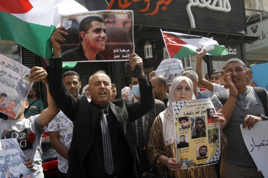 Palestinians seen holding portraits showing prisoners,